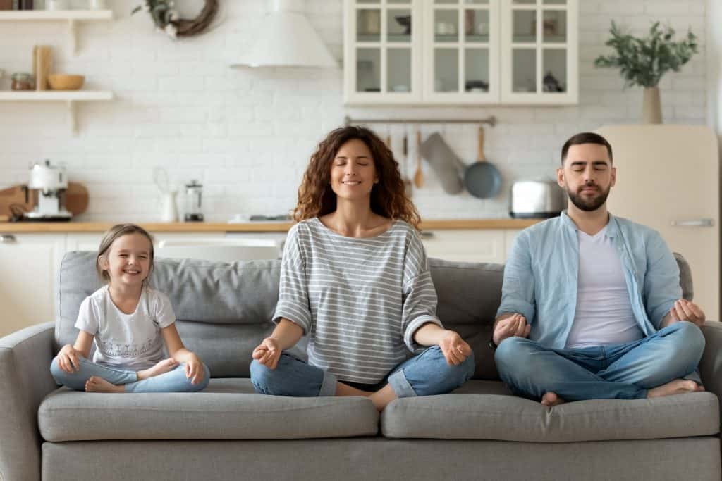 an image of a family performing meditation